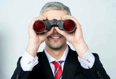 Businessman viewing through binoculars stock vector