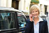 Usměvavá podnikatelka mluví přes mobil