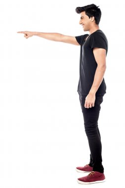 Casual young man pointing to his side