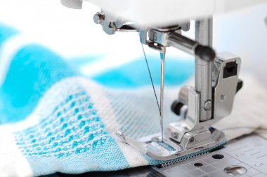 Sewing machine closeup with blue fabric on white background