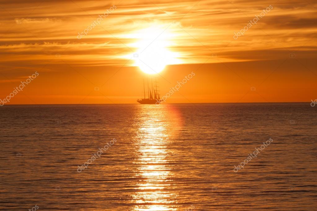 Sail ship silhouette at sea and sun