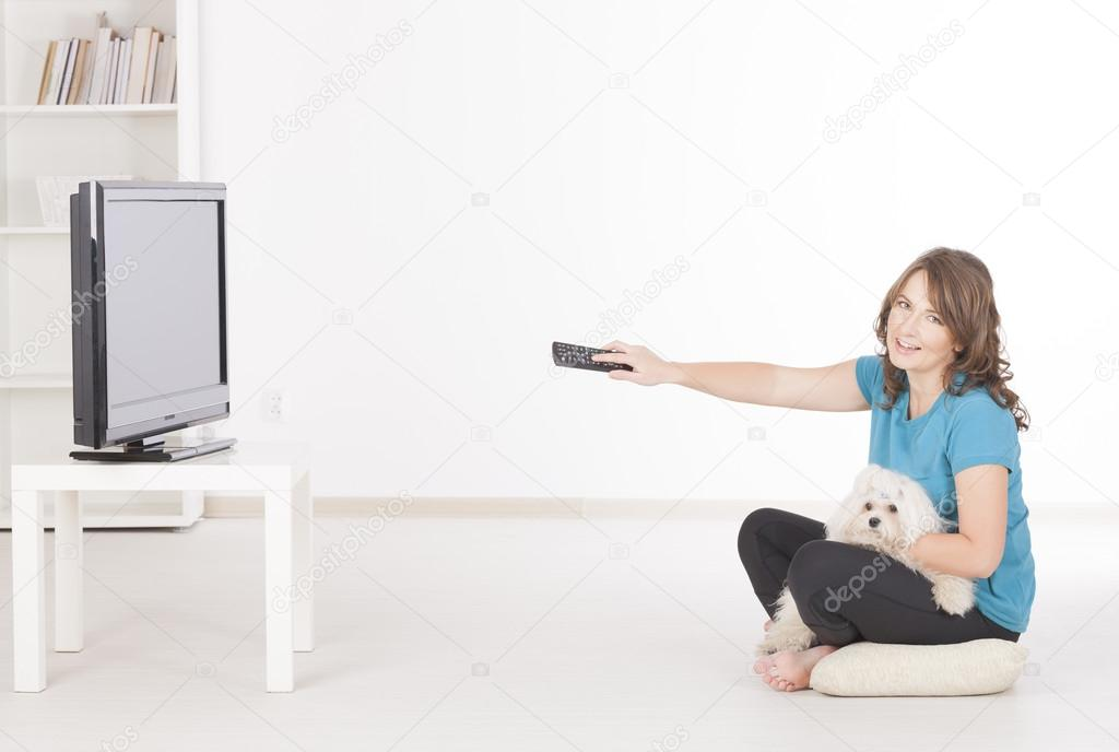 Woman and dog watching TV together