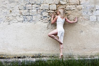 Barefoot blond girl along a wall.