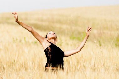 Graceful and sexy woman in a wheat field.