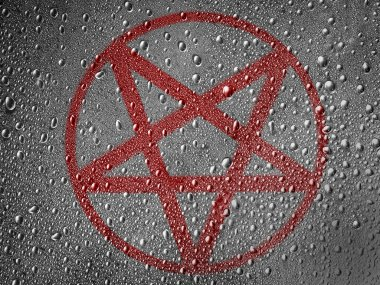 Pentagram symbol painted on metal surface covered with rain drops