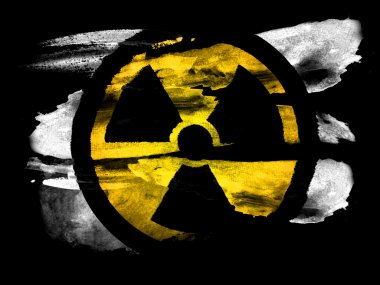 Nuclear radiation symbol painted on black textured paper with watercolor