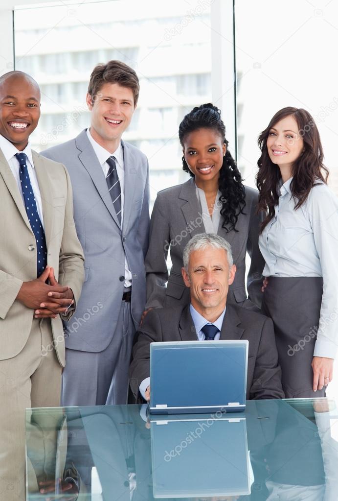 8f382c0315 Gestionnaire souriant assis au bureau derrière un ordinateur portable et  entouré de son équipe — Image de ...