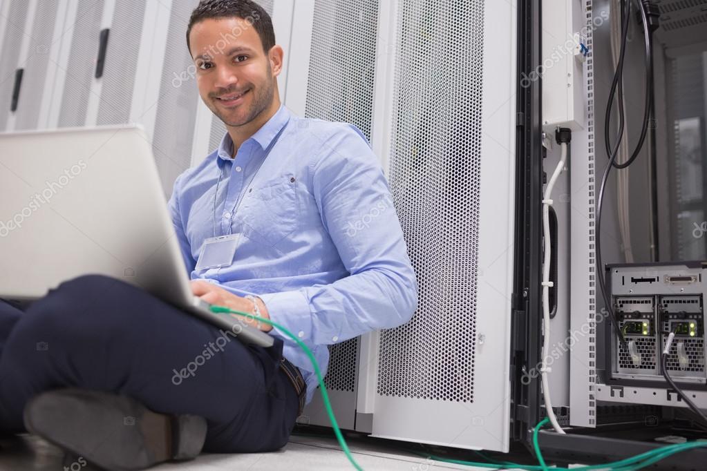 heureux technicien travaillant sur ordinateur portable connect au serveur photographie. Black Bedroom Furniture Sets. Home Design Ideas