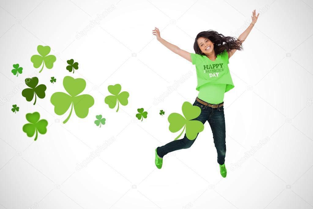 girl wearing patricks day t shirt jumping for joy stock photo
