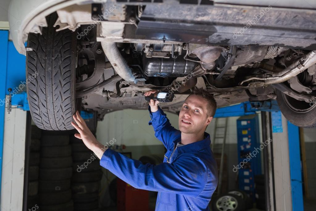 mechanic with flashlight under car stock photo wavebreakmedia