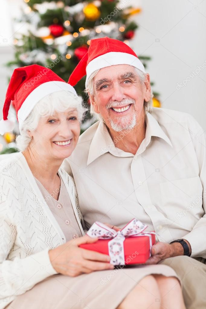 smiling old couple swapping christmas gifts stock photo