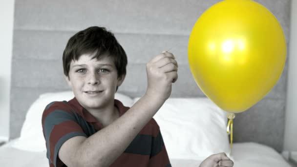 Jongen zijn ballon piercing in de slaapkamer in selectieve kleur
