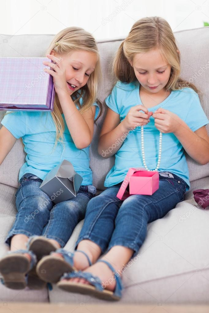 Twins Unwrapping Birthday Gift Sitting On A Couch Stock Photo