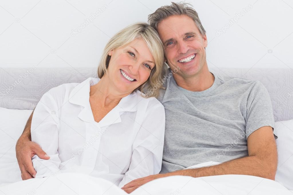 heureux couple au lit photographie wavebreakmedia 28058447. Black Bedroom Furniture Sets. Home Design Ideas