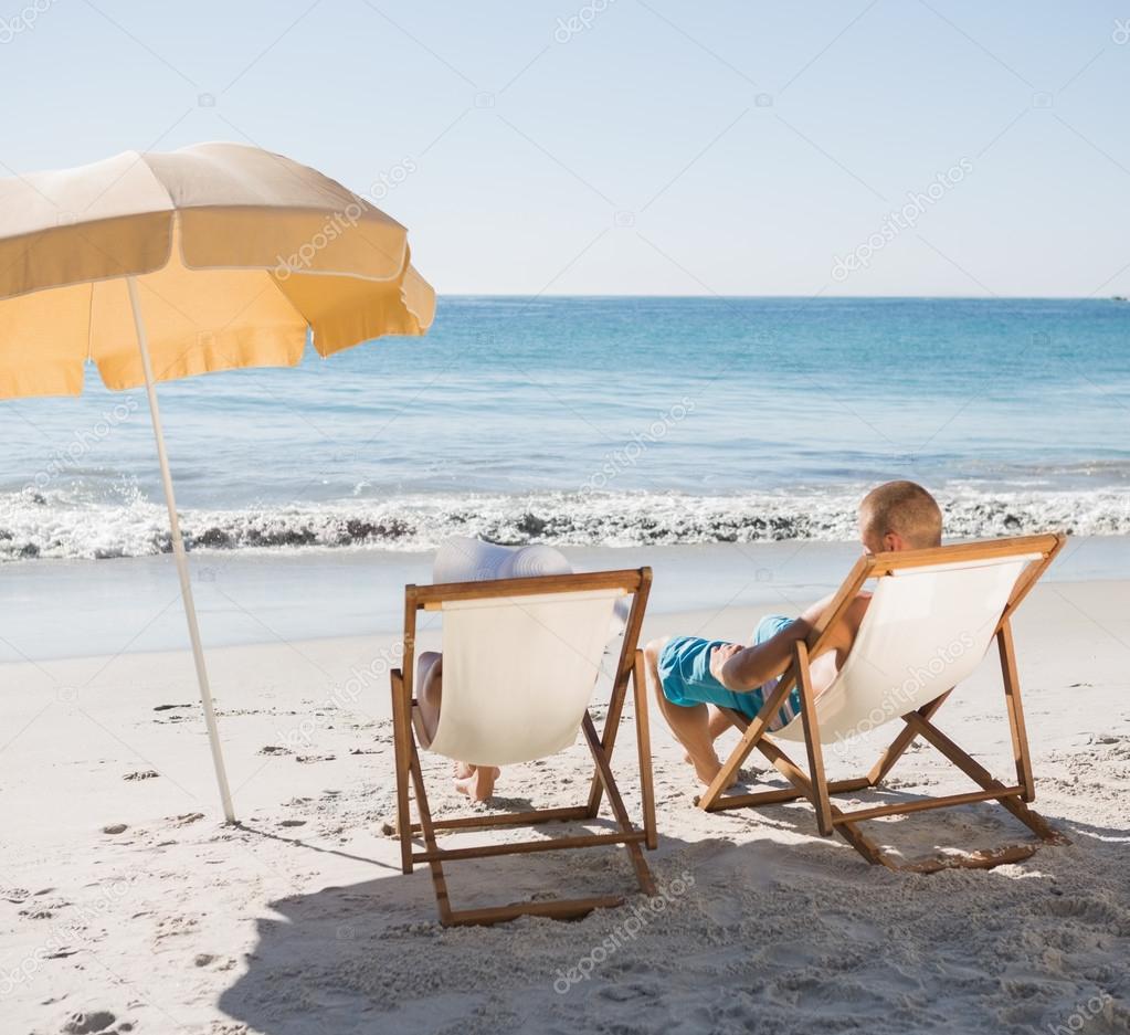 Cute Couple On The Beach Sunbathing On Their Deck Chairs U2014 Photo By  Wavebreakmedia
