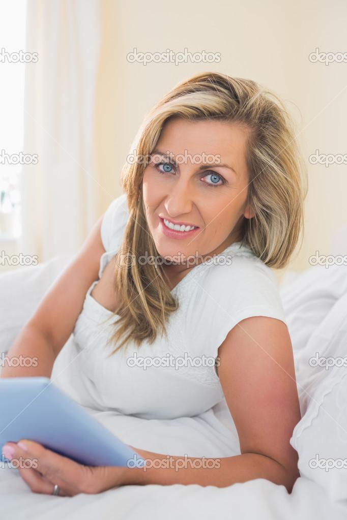 Donna di piacere guardando fotocamera utilizzando un tablet pc sdraiato sul suo letto foto - Foto di donne sul letto ...