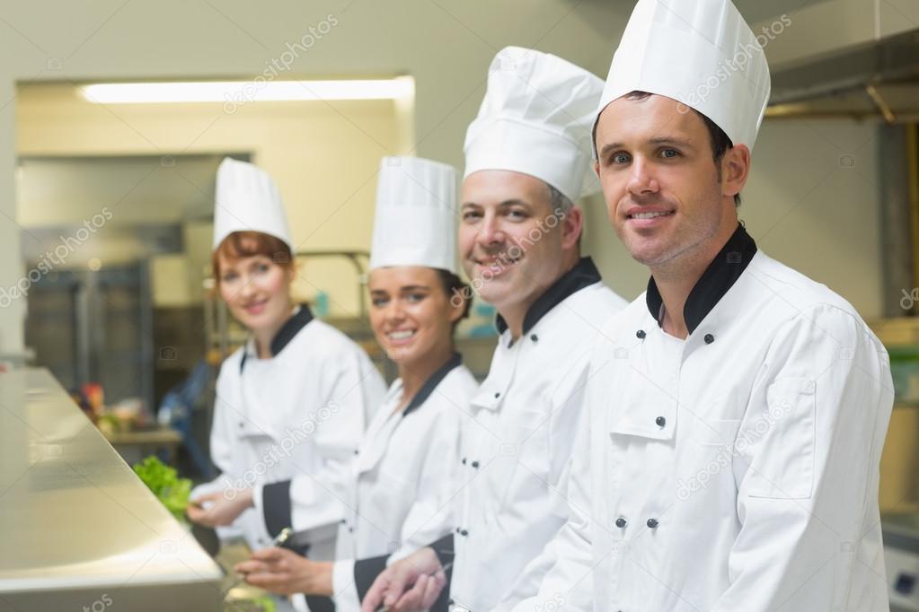 vier Köche arbeiten in einer Küche stehen in einer Zeile — Stockfoto ...