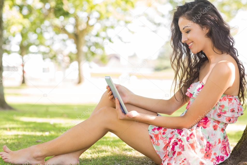 stylish cute brunette sitting under a tree using tablet — stock