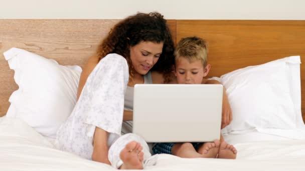 m re et fils allong sur un lit video 116074064. Black Bedroom Furniture Sets. Home Design Ideas