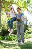 šťastná matka lítací dcera v parku