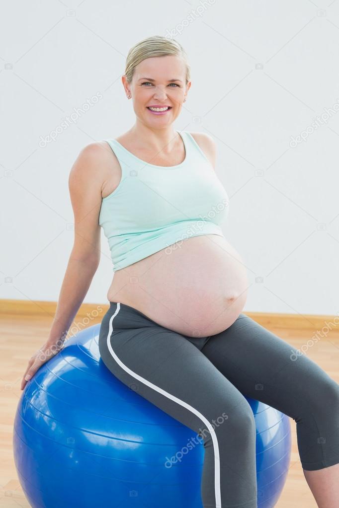 Feliz rubia mujer embarazada sentada sobre bola azul ejercicio en un  gimnasio - foto  sentado en el embarazo pelota — Foto de Wavebreakmedia —  Foto de ... 3df213239d57