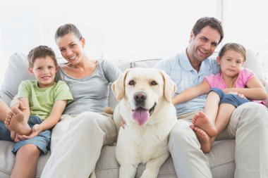 Happy family sitting on couch with their pet labrador