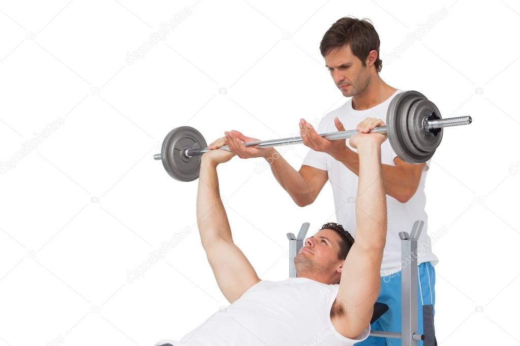 Фотообои Trainer helping fit man to lift the barbell bench press