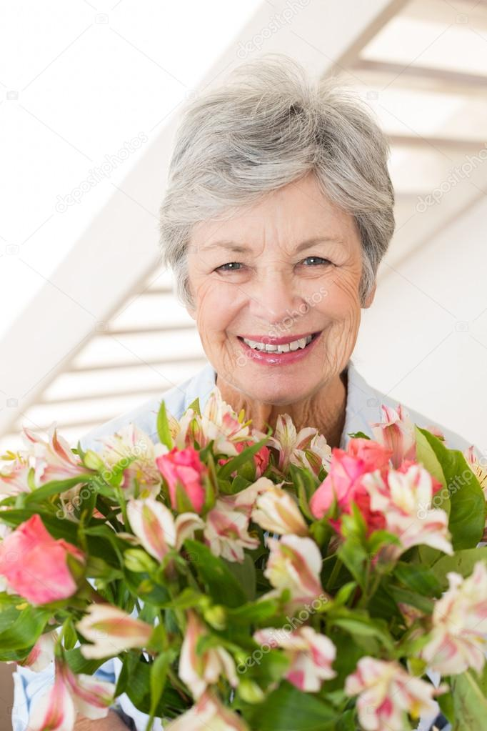 Pensione donna con bouquet di fiori sorridendo alla for Piani di pensione gratuiti
