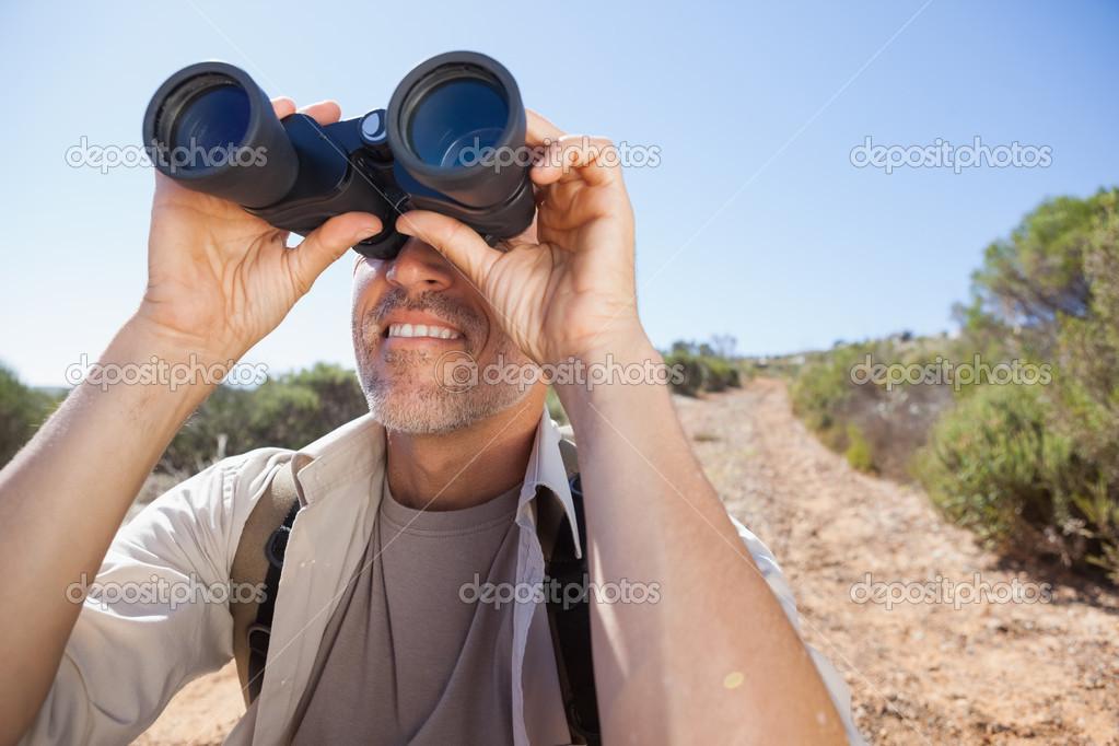 Wanderer durch sein fernglas auf land trail u stockfoto