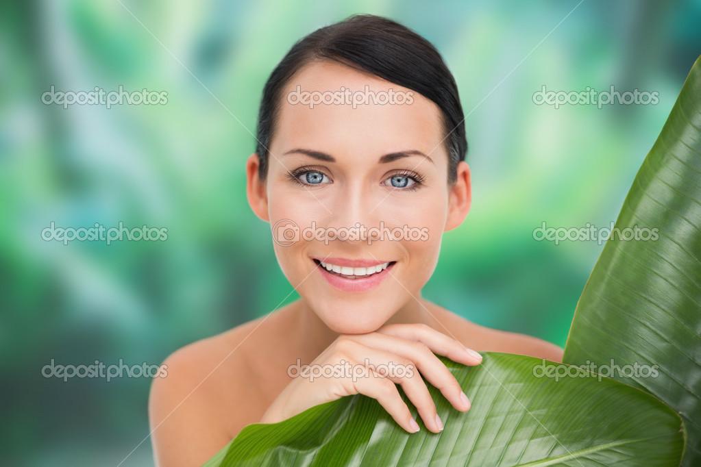 Schöne nackte Brünette posiert mit grünen Blättern