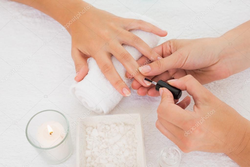Cerca de esteticista aplicando esmalte para las uñas del cliente femenino en salón de belleza spa — Foto de Wavebreakmedia