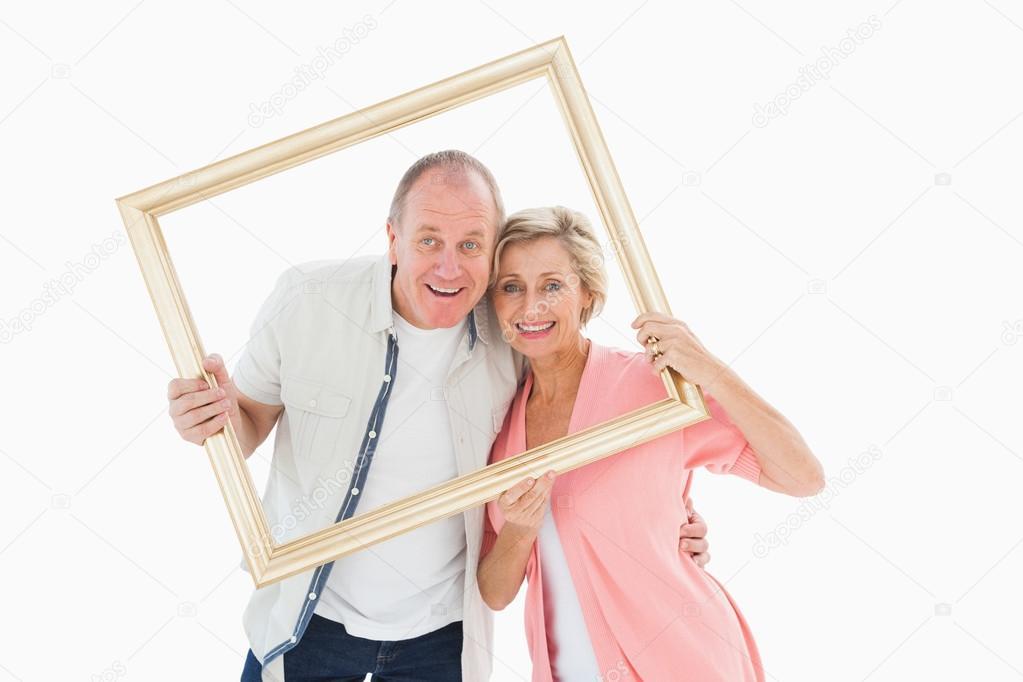 pareja mayor sonriendo a la cámara a través de marco — Foto de stock ...