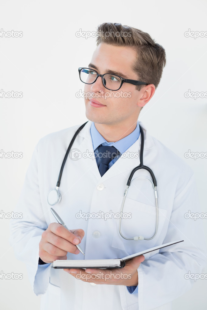 7c7f52ef5512 Smiling young doctor writing in notebook — Stock Photo ...