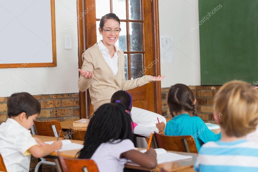 teacher talking to the pupils in classroom stock photo