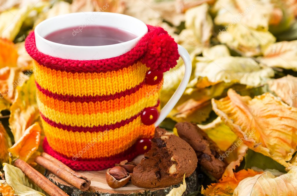 Fruit tea in a cup in a knitted cover