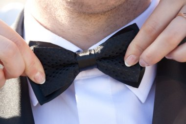 Women's hands touches bow-tie on a suit.