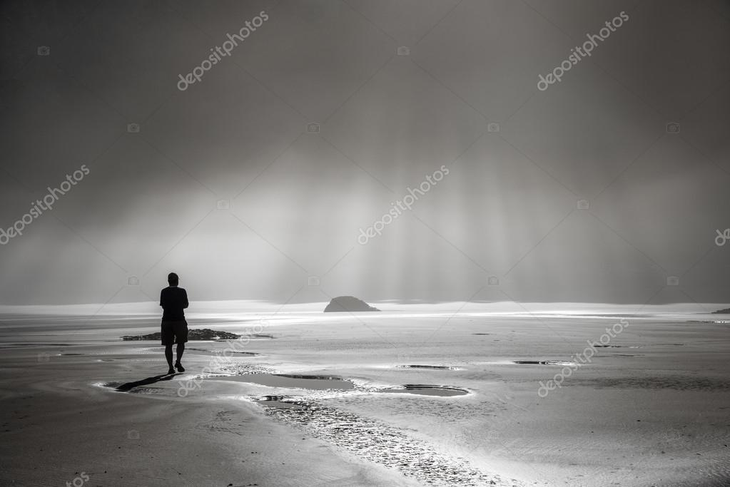 Person walking toward sunbeams