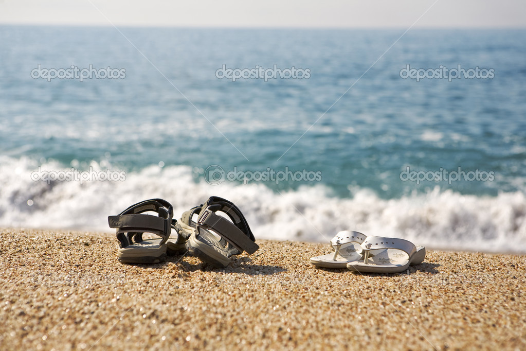 8e9a1e501 A photo of two pairs of beach shoes at the seaside — Photo by ...
