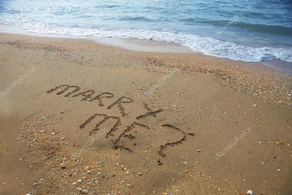 Marry Me written on sandy beach