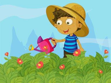 A boy watering the plants in a garden