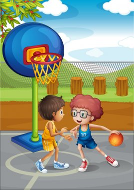 Two boys playing basketball at the basketball court