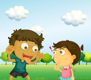 A boy annoying a little girl