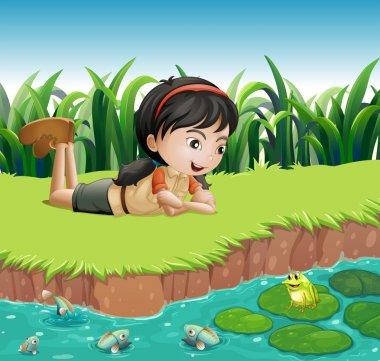 A girl beside a pond