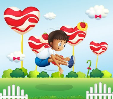 A boy jumping in the field with giant lollipops