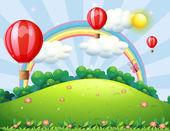 Fotografia palloni galleggianti in cima alla collina con un arcobaleno