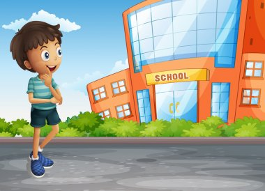 A young boy at the street across the school building