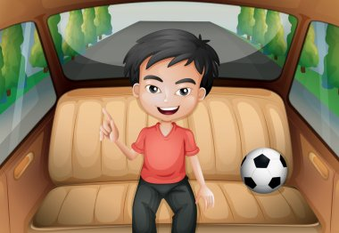 A boy inside the car with a soccer ball