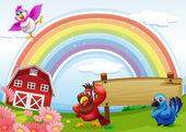 Fotografia uccelli in fattoria con un arcobaleno e un cartello vuoto