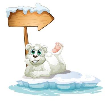 A smiling polar bear under the wooden arrow