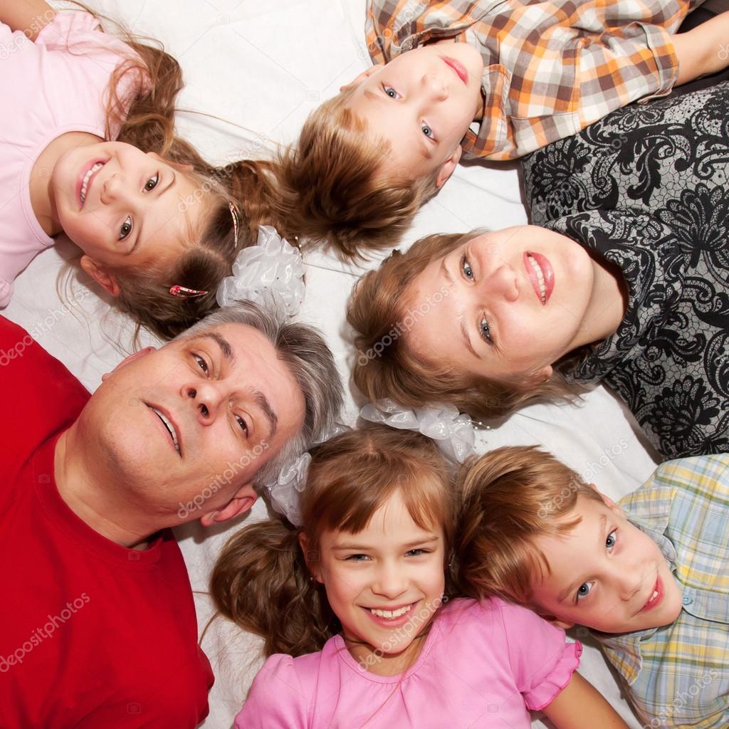 a0b7000ee4f55 Heureuse famille couché n un cercle sur le sol. père